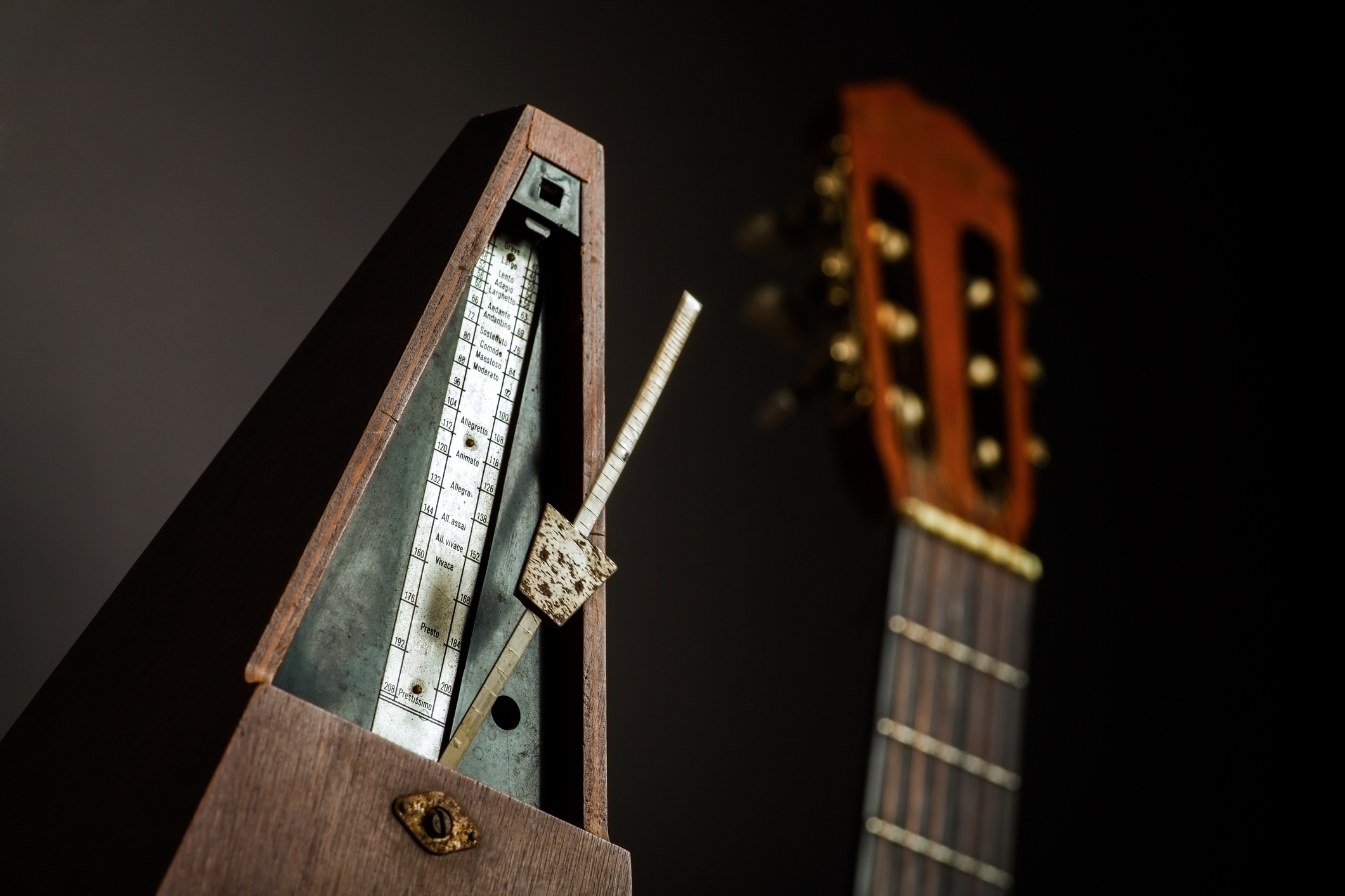 Color shot of a vintage metronome, next to an acoustic guitar, on a black background.